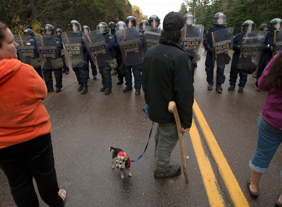 Protesters face a line of police officers in Rexton, N.B. on Thursday, Oct. 17, 2013. (Andrew Vaughan / THE CANADIAN PRESS)