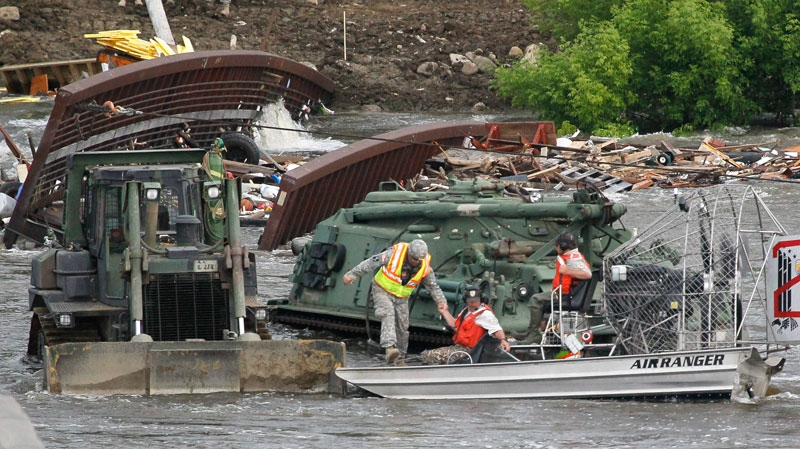 Officials with the U.S. Dept. of Fish and Wildlife use a fan boat to transport North Dakota National Guard Engineers off their equipment after securing cables to a pedestrian bridge over the flooding Souris River in Minot, N.D., Saturday, June 25, 2011. (AP / Charles Rex Arbogast)