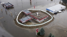 In this aerial photo, a Conoco gas station is surrounded by sand bags, the flood waters of the Souris River, and an oil slick Friday, June 24, 2011 in Minot, N.D. (AP Photo/Charles Rex Arbogast)