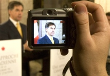 A reporter uses a digital camera to record Industry Minister Jim Prentice as he announces amendments to the Copyright Act on Parliament Hill in Ottawa, Thursday, June 12, 2008. (Tom Hanson / THE CANADIAN PRESS)