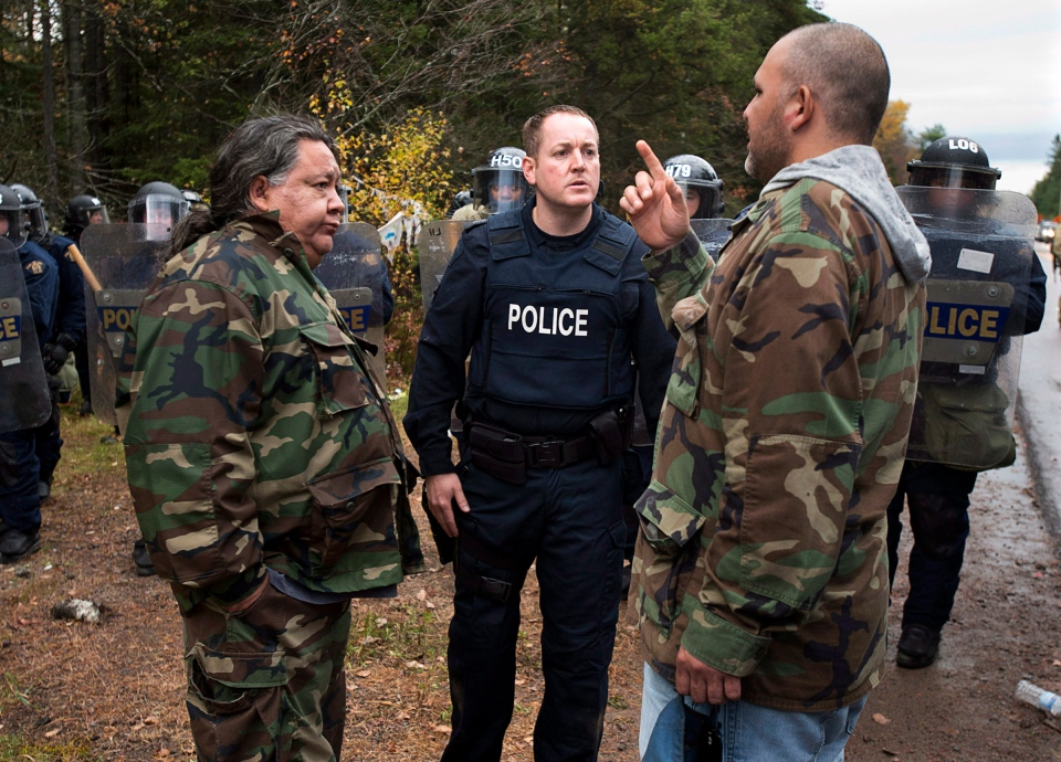 Negotiations between protesters and police in Rexton, N.B. as police began enforcing an injunction to end an ongoing demonstration against shale gas exploration in eastern New Brunswick on Thursday, Oct.17, 2013. (Andrew Vaughan / THE CANADIAN PRESS)