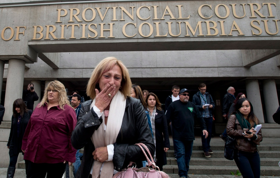 Rachael Szendrei, the mother of Laura Szendrei, blows a kiss to her deceased daughter as she leaves court following verdict at the provincial court in Surrey, B.C., on Friday, Oct. 18, 2013. (Jonathan Hayward / THE CANADIAN PRESS)