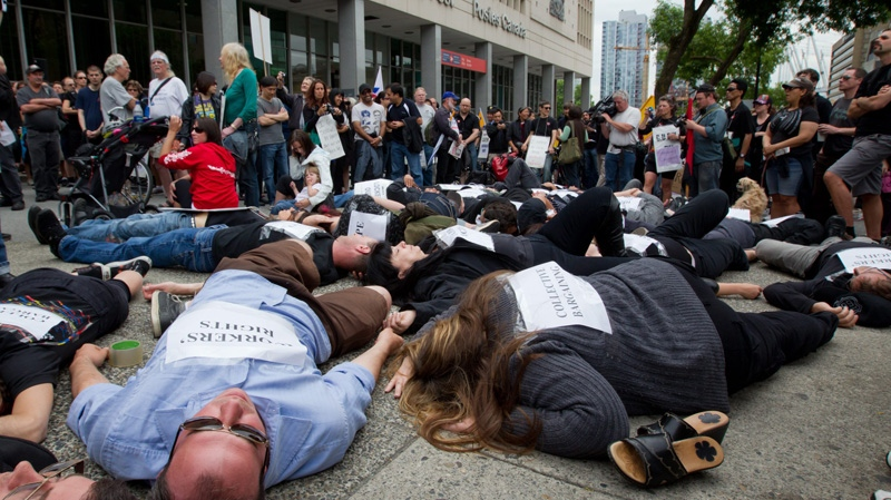 Canada Post employees hold a 'die-in' during a rally outside the main post office in Vancouver, B.C., on Monday, June 27, 2011. (Darryl Dyck / THE CANADIAN PRESS)