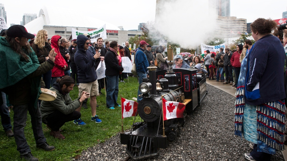 Protesters, demonstrating against Enbridge's application to reverse it's Line 9 pipeline, watch as a toy train goes through their ranks as part of its regular route outside Toronto's Metro Convention Centre on Saturday, October 19, 2013. (Chris Young / THE CANADIAN PRESS