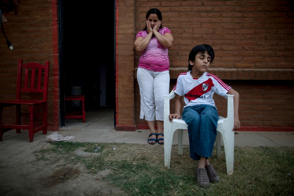 In this April 1, 2013, photo, Silvia Alvarez leans against her red brick home while keeping an eye on her son, Ezequiel Moreno, who was born with hydrocephalus, in Gancedo, in Chaco province, Argentina.  (AP Photo/Natacha Pisarenko)