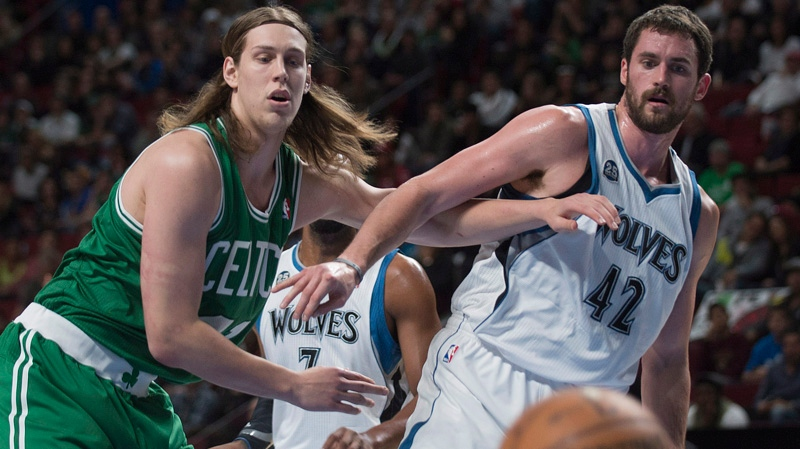 Minnesota Timberwolves' Kevin Love, right, and Boston Celtics' Kelly Olynyk keep their eyes on the ball during first quarter NBA pre-season basketball action in Montreal, Sunday, October 20, 2013. THE CANADIAN PRESS/Graham Hughes