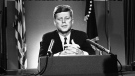 In this July 26, 1963 file photo, U.S. President John F. Kennedy sits behind microphones at his desk in Washington after finishing his radio-television broadcast to the nation on the nuclear test ban agreement initialed by negotiators in Moscow. (AP Photo/John Rous)