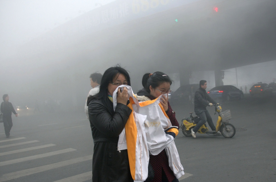 Two women cover up their mouths and noses with a jacket as they cross a street covered by dense smog in Harbin, northern China, Monday, Oct. 21, 2013.. (AP Photo/Kyodo News)