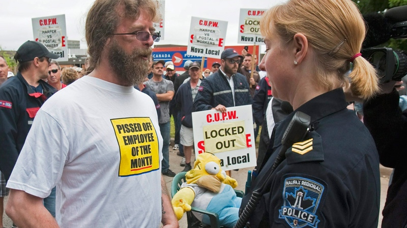 A locked out Canada Post employee talks with a police officer outside the main postal facility in Halifax on Monday, June 27, 2011. (Andrew Vaughan / THE CANADIAN PRESS)
