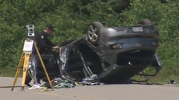 A police officer examines the scene of a fatal crash on Highway 60, near Algonquin Park, Monday, June 27, 2011.