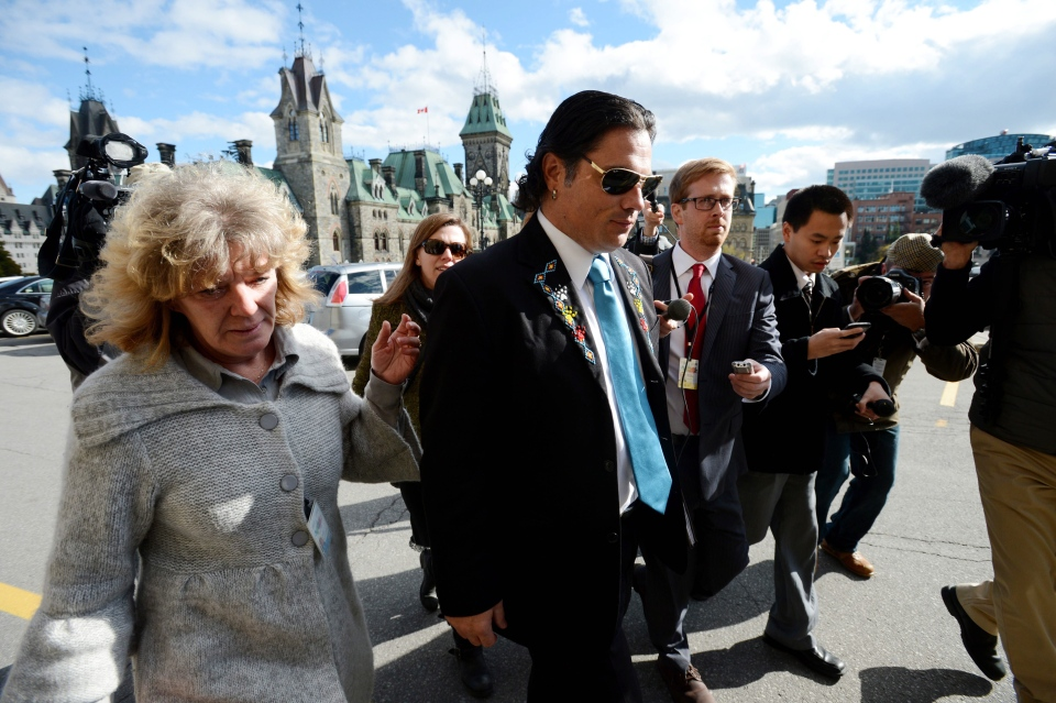 Sen. Patrick Brazeau is escorted into the building as he arrives to Parliament Hill in Ottawa on Tuesday, Oct. 22, 2013. (Sean Kilpatrick / THE CANADIAN PRESS)