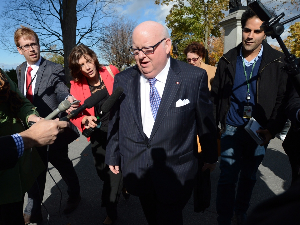 Sen. Mike Duffy is questioned by media as he arrives at the Senate on Parliament Hill in Ottawa on Tuesday, Oct. 22, 2013. (Sean Kilpatrick / THE CANADIAN PRESS)