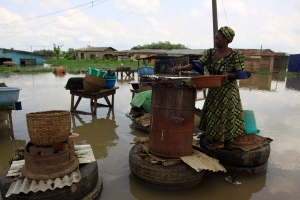 A woman prepares meat for sale near flooded houses after a heavy downpour in Ikorodu, Nigeria Wednesday, Oct. 26, 2011. (AP / Sunday Alamba)