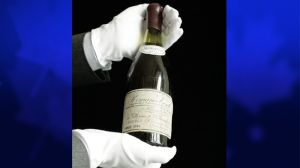 A Christie's employee presents a bottle of Romanee-Conti 1945 in Geneva, Switzerland, Friday, May 11, 2007. (AP / Keystone, Martial Trezzini)