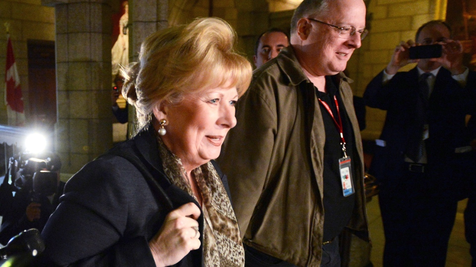 Sen. Pamela Wallin is escorted by assistant Mark Fisher as she arrives at the Senate on Parliament Hill in Ottawa on Wednesday, Oct. 23, 2013. (Sean Kilpatrick / THE CANADIAN PRESS)