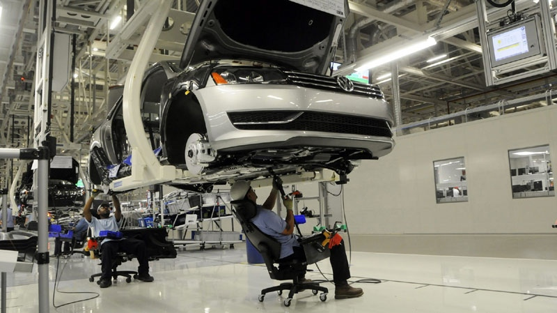 Workers inspect the undercarriage of a new Passat inside the new Volkswagen plant in Chattanooga, Tenn. on Tuesday, May 24, 2011. (AP Photo/Billy Weeks)