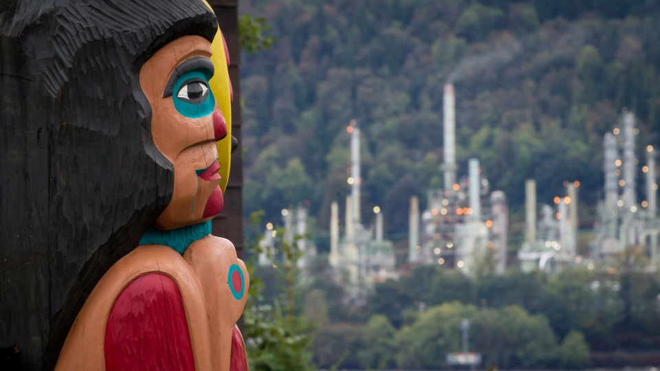 A totem pole on the Tsleil-Waututh First Nation that was a gift from the Lummi Nation in Washington state, frames the Chevron Burnaby Oil Refinery in the distance after the totem was unveiled during a ceremony in North Vancouver, B.C., on Sunday, Sept. 29, 2013. (Darryl Dyck / THE CANADIAN PRESS)