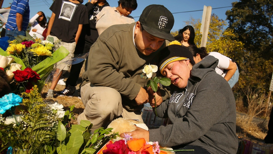 Sujey Lopez and her husband Rodrigo Lopez mourn for their son by a memorial set up at the site where their 13-year-old son, Andy Lopez, was shot and killed by a Sonoma County sheriff's deputy, Wednesday Oct. 23, 2013, in Santa Rosa, Calif. (AP / The Press Democrat, Conner Jay)