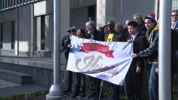 This year's Manitoba Heroes awards winners help raise a ceremonial flag at City Hall on Friday.