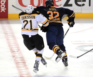 Buffalo Sabre, John Scott (32) checks Boston Bruin, Loui Eriksson (21) during third period action against at the First Niagara Center on Wednesday, Oct. 23, 2013. (AP / Harry Scull Jr. Buffalo News)