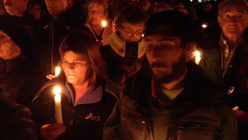 A crowd of mourners attend a candlelit vigil for a homeless man killed in a fire in Berwick, N.S., on Saturday, Oct. 26, 2013.
