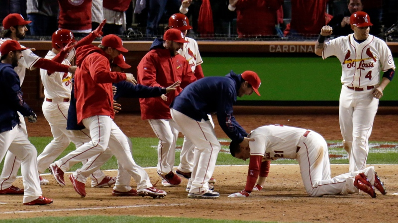 Teammates mob St. Louis Cardinals' Allen Craig at home after Craig scored the game-winning run on an obstruction call during the ninth inning of Game 3 of baseball's World Series against the Boston Red Sox Saturday, Oct. 26, 2013, in St. Louis. (AP / Charlie Riedel)