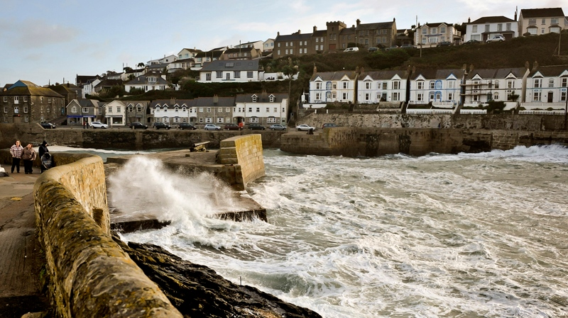 People walk along a path as waves crash onto a seawall protecting the harbor of Porthleven, Cornwall, southwest England, Sunday, Oct. 27, 2013. (PA, Ben Birchall)