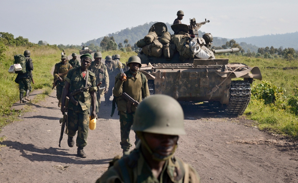 Congolese army soldiers march past a tank aimed towards Kibumba Hill, which is occupied by M23 rebels, around 25 kilometres from the provincial capital Goma, in eastern Congo, Sunday, Oct. 27, 2013. (AP / Joseph Kay)