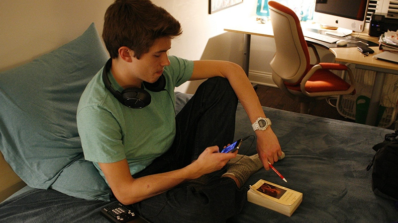 Donald Conkey, 15, checks his smartphone while doing homework in his bedroom on Monday, March 11, 2013, in Wilmette, Ill. (AP Photo/Martha Irvine)