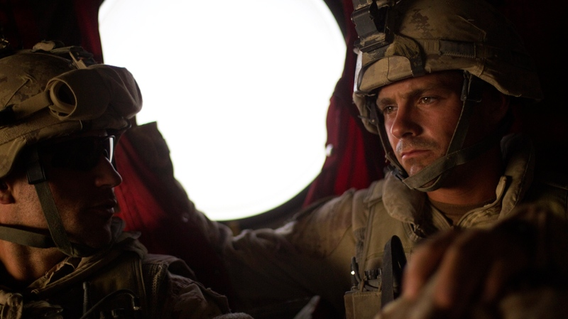 Canadian Army's 1st Battalion Royal 22nd Regiment Cpl. Frederic Bouchard, 24, of Quebec, Canada, right, looks out of a helicopter as it takes off from Forward Operating Base Sperwan Ghar as he begins his journey home Thursday, June 30, 2011 in the Panjwaii district of Kandahar province, Afghanistan. (AP / David Goldman)