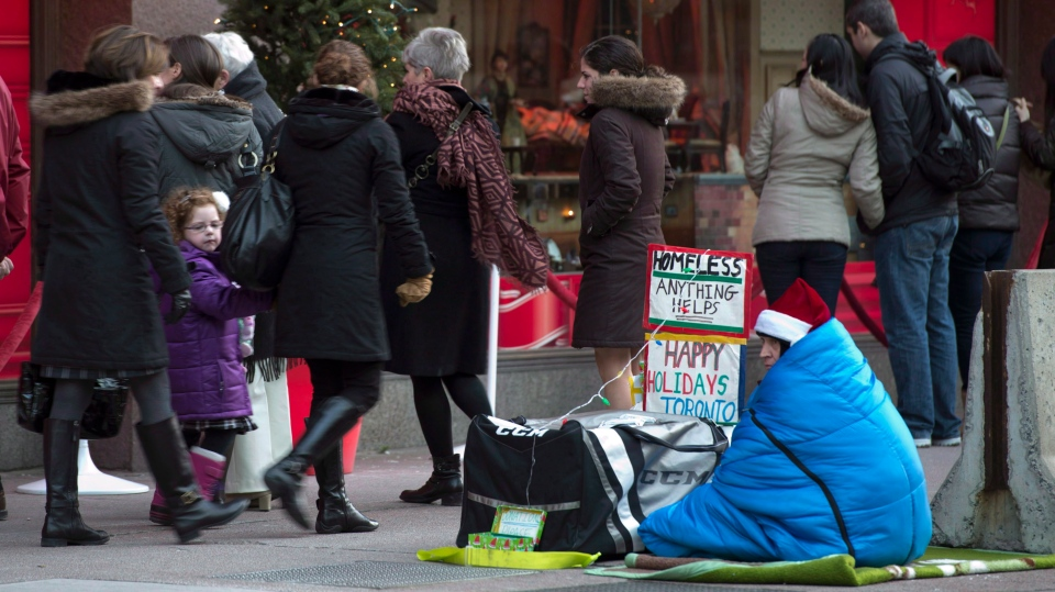 A homeless person sits on the sidewalk as holiday shoppers admire displays in the windows of a downtown department store in Toronto on Sunday, Dec. 23, 2012. (Frank Gunn / THE CANADIAN PRESS)