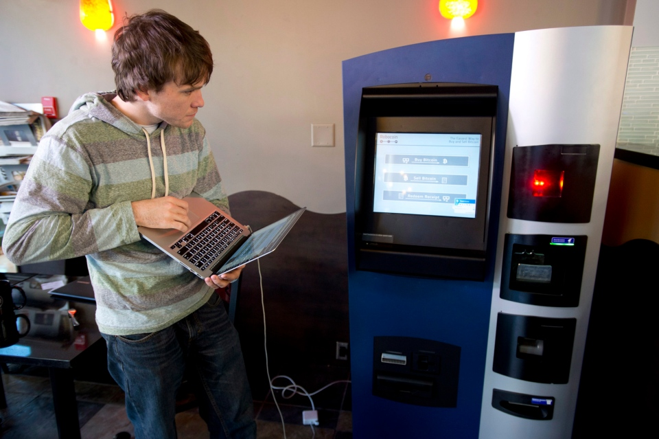 John Russell, co-founder of Robocoin, works out the kinks of what is being billed as the world's first Bitcoin ATM at a coffee shop in Vancouver, Tuesday, Oct. 29, 2013. (Jonathan Hayward / THE CANADIAN PRESS)