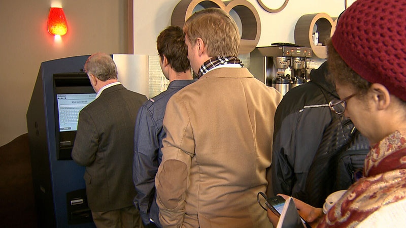 Bitcoin users lineup at the world's first ATM for the virtual currency at a Vancouver coffee shop. Oct. 29, 2013. (CTV)