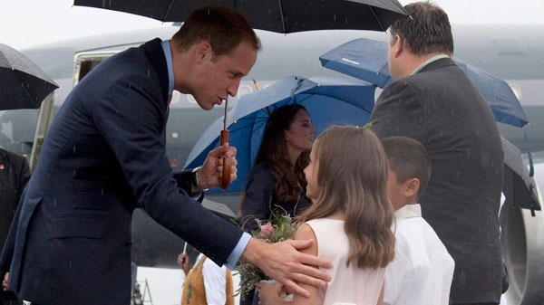 The Duke of Cambridge receives flowers from Amelie Wood, 8, as he arrives at the airport in Yellowknife, N.T. (Jonathan Hayward /THE CANADIAN PRESS)