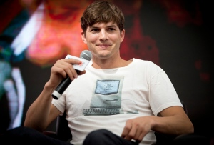 """American actor Ashton Kutcher, who portrays Apple's Steve Jobs in the film """"Jobs"""" smiles at a promotional event hosted by the Macworld iWorld expo in Beijing, China, Sunday, Aug. 25, 2013. (AP Photo/Andy Wong)"""