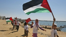 Palestinian children fly Palestinian and Turkish flags to show their support for the flotilla attempting to reach the Gaza Strip, in the port of Gaza City Saturday, July 2, 2011. (AP / Hatem Moussa)