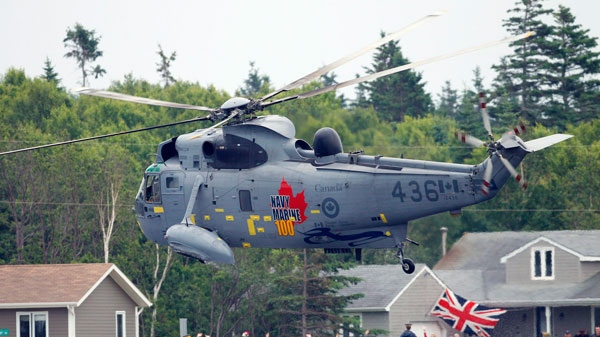 Spectators cheer as a helicopter piloted by Prince William, the Duke Cambridge, flies by during a training exercise in Dalvay-by-the-Sea on Prince Edward Island as part of their Royal Tour of Canada, Monday, July 4, 2011. (AP / Robert F. Bukaty)