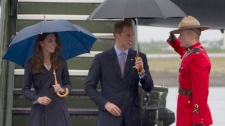 The Duke and Duchess of Cambridge are saluted by an RCMP officer as they arrive in Yellowknife, N.T. (Jonathan Hayward THE CANADIAN PRESS)