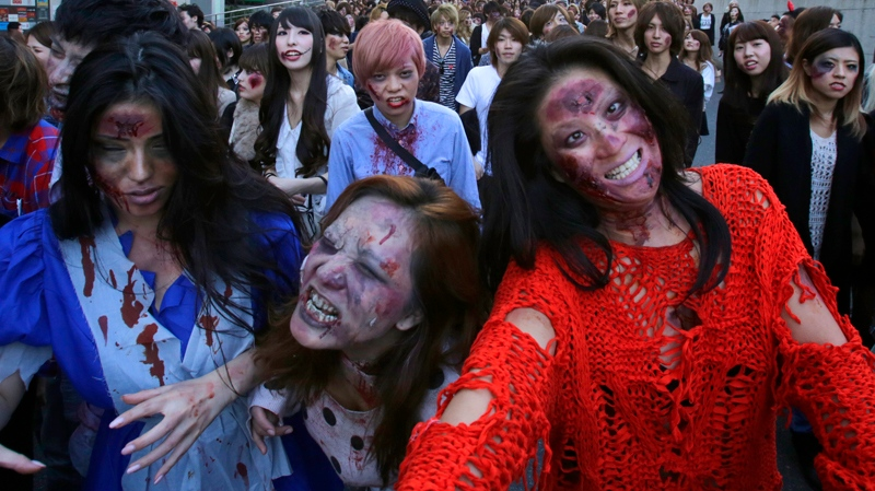 Participants wearing zombie makeup, perform during a Halloween event at Tokyo Tower in Tokyo, Thursday, Oct. 31, 2013. (AP / Shizuo Kambayashi)