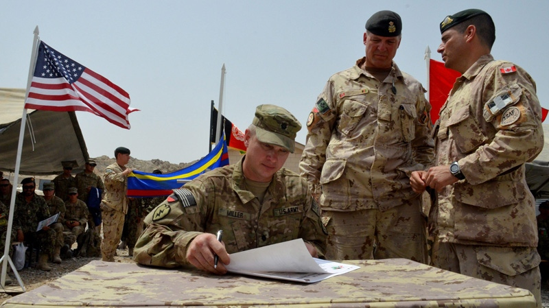 Lt.-Col. Michel-Henri St-Louis, the commander of the 1st Battalion Royal 22e Regiment battle group (right) and Brig.-Gen. Dean Milner, commander of Canadian troops in Afghanistan (centre), watch as Lt.-Col. Steve Miller, who is charge of the 3rd Battalion 21st U.S. Infantry Regiment (seated) signs transfer of authority papers on Tuesday, July 5, 2011. (Murray Brewster / THE CANADIAN PRESS)