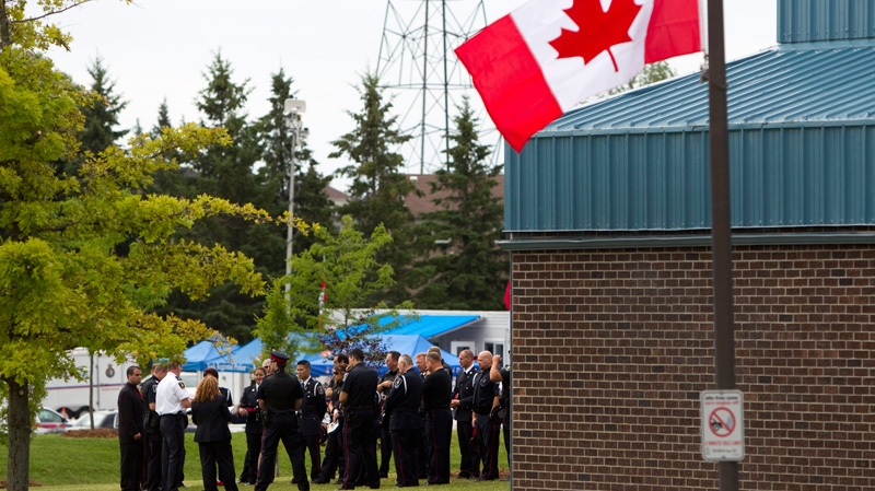 The Canadian flag flies at half-mast as police officers gather for the Remembrance Service for York Regional Police Officer Constable Garrett Styles outside the Ray Twinney Complex in Newmarket, Ont., Tuesday July 5, 2011. (Darren Calabrese / THE CANADIAN PRESS)