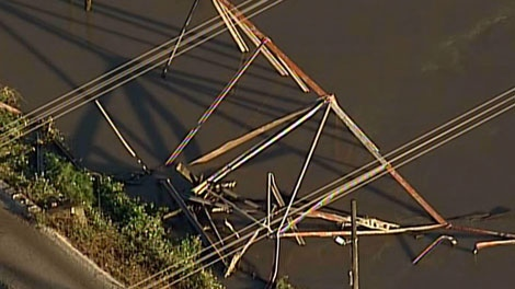 A hydro transmission tower lies in the Fraser River after river erosion caused it to topple. July 5, 2011. (CTV)