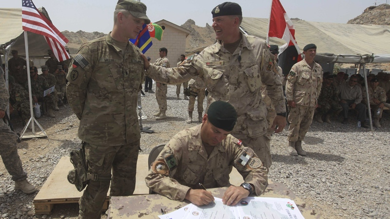 From right, Brig.-Gen Dean Milner, Commander of Canadian forces in Afghanistan, Lt.Col. Michel Henri St- Louis and U.S Col. Steve Miller are seen during the transfer of command authority papers at the forward fire base Masum Ghar in Panjwaii district in Kandahar province Afghanistan, Tuesday, July 5, 2011. (AP Photo/Rafiq Maqbool)