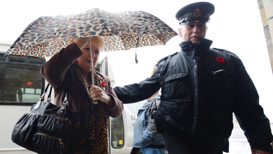 Sen. Pamela Wallin shields herself from the rain as she arrives at the Senate on Parliament Hill  in Ottawa on Thursday, October 31, 2013. (Sean Kilpatrick / THE CANADIAN PRESS)