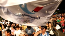 South Koreans gather to watch TV for the International Olympic Committee to announce the 2018 Winter Olympic site in Chuncehon, South Korea, Wednesday, July 6, 2011. (AP / Ahn Young-joon)