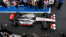 McLaren Mercedes driver Jenson Button, of Britain drives into the winner's circle after winning the Canadian Grand Prix, Sunday, June 12, 2011 in Montreal. (Paul Chiasson / THE CANADIAN PRESS)