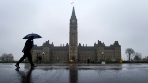 A pedestrian walks by Parliament Hill in Ottawa, Thursday, Oct. 31, 2013. (Sean Kilpatrick / THE CANADIAN PRESS)