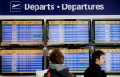 Passengers stand next to a departures board at Trudeau Airport in Montreal on Friday, April 13, 2012. (The Canadian Press/Graham Hughes)