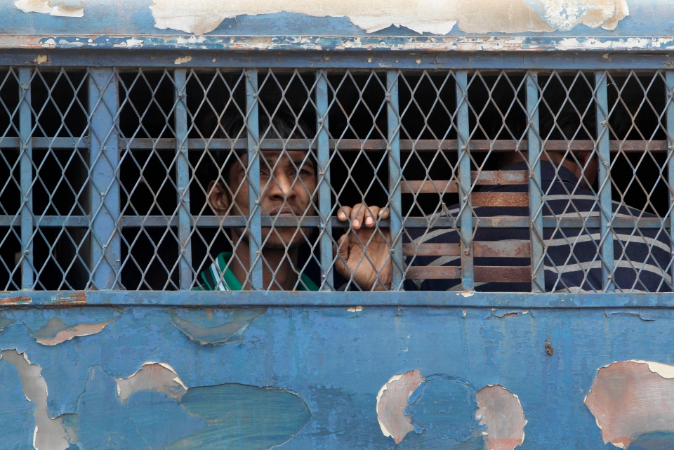 A Bangladeshi border guard looks through the window of a prison van as he leaves a special court after a verdict in Dhaka, Bangladesh, Tuesday, Nov. 5, 2013. (AP Photo/A.M. Ahad)