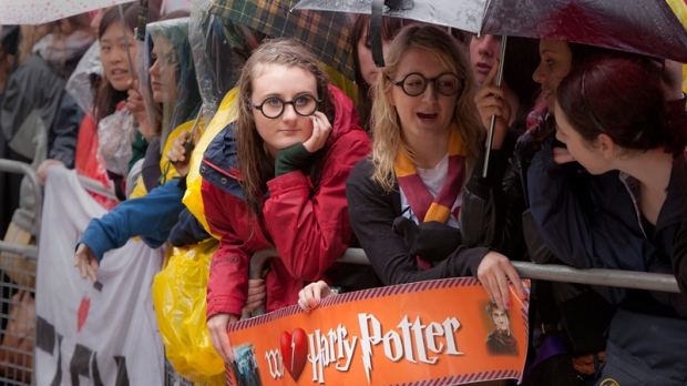 Harry Potter fans wait with umbrellas in the rain outside the cinema in Leicester Square, central London, for the world premiere of 'Harry Potter and The Deathly Hallows: Part 2,' the last film in the series, Thursday, July 7, 2011. (AP / Joel Ryan)